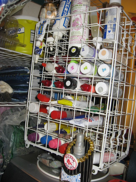 Paint Storage rack #12 with adhesives and paint on top of Roll top desk #4